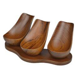 Stojánek na 3 dýmky Hand, teak-Stylový dřevěný stojánek na tři dýmky. Nádherně zpracovaný stojánek na dýmky je vyrobený z teakového dřeva. Díky prostoru na jednotlivé dýmky, který je ve tvaru hluboké lžičky, bude dýmka ideálně opřená. Ručně leštěný hladký povrch v polomatném provedení je v hnědém odstínu s výraznými léty. Praktická pomůcka kuřáka dýmky a současně krásný doplněk interiéru. Dýmkový stojánek je dodávaný v krabici. Rozměr 17,5x7x11,5cm.