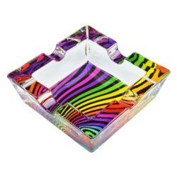 Cigaretový popelník skleněný Waves-Cigaretový popelník skleněný Waves. Hranatý popelník na cigarety se čtyřmi odkládacími místy je vyrobený ze silného skla. Díky větší šířce dvou odkládacích míst, je tento popelník vhodný také pro doutníky. Tloušťka stěny je 1,4cm. Dno popelíku je potištěné atraktivním barevným motivem. Rozměry popelníku: 10x10x3,1cm. Popelník je dodávaný v kartonové krabičce.