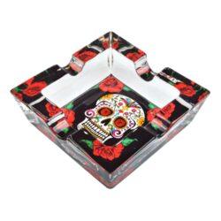Cigaretový popelník skleněný Skull-Cigaretový popelník skleněný Skull. Hranatý popelník na cigarety se čtyřmi odkládacími místy je vyrobený ze silného skla. Díky větší šířce dvou odkládacích míst, je tento popelník vhodný také pro doutníky. Tloušťka stěny je 1,4cm. Dno popelíku je potištěné atraktivním barevným motivem. Rozměry popelníku: 10x10x3,1cm. Popelník je dodávaný v kartonové krabičce.