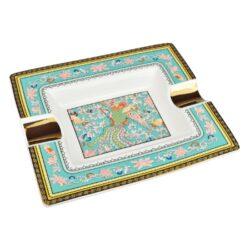 Doutníkový popelník keramický Peacock-Atraktivní doutníkový popelník na 2 doutníky. Hranatý keramický popelník ve tvaru obdélníku s barevným motivem páva je zdobený zlatými prvky. Kvalitně zpracovaný glazurovaný povrch popelníku je v lesklém provedení. Popelník na doutníky je dodávaný v dárkové krabičce. Rozměry popelníku: 20,5x17,2x3,1cm.