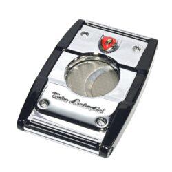 Doutníkový ořezávač Lamborghini Precisione, chrom-černý-Elegantní ořezávač na doutníky Tonino Lamborghini Precisione. Silné tělo dvoubřitého ořezávače je precizně vyrobené z kvalitní nerezové oceli. Jednoduchým stisknutím tlačítka dolů, které současně slouží jako pojistka proti otevření, uvolníte čepele od sebe a ořezávač je připraven k použití. Dvojité velmi ostré gilotinové nože, jsou zárukou rychlého a čistého řezu doutníku. Max. průměr otvoru pro doutník 2cm. Doutníkový ořezávač je dodáván v kožené krabičce vyložené jemným sametem. Rozměry zavřeného ořezávače: 6,5x4cm.