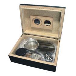 Doutníkový Humidor Set černý 25D, stolní-Doutníkový Humidor Set. Stolní humidor na doutníky s kapacitou cca 25 doutníků. Sada obsahuje: popelník, vlhkoměr, zvlhčovač a ořezávač. Vnitřek humidoru je vyložený cedrovým dřevem.  Rozměr: 24x18x8 cm.